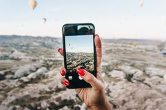 Woman taking photo of Hot air balloons festival on smartphone,. Cappadocia, Turkey stock photos
