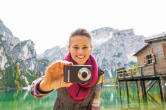 Woman taking photo on lake braies in south tyrol Royalty Free Stock Images
