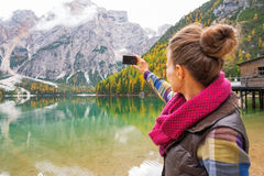 Woman taking photo on lake braies in south tyrol Royalty Free Stock Photo