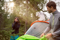 Woman taking photo of man near hanging tent camping with sun flare. Group of friends people summer adventure journey in. Woman taking photo of men near hanging stock photo