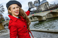 Woman taking photo with mobile phone on embankment in Paris Royalty Free Stock Photo