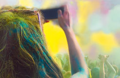 Woman taking photo on mobile phone on holi color festival Stock Photos