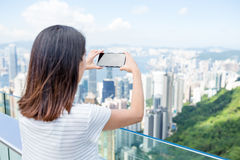 Woman taking photo with mobile phone in the peak of Hong Kong Stock Image