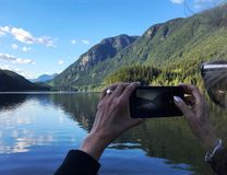 Woman taking photo of mountain lake with mobile phone. Woman photographing lake with mobile phone royalty free stock photos