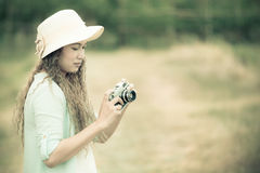 Woman taking photo of nature scene vintage style processed Royalty Free Stock Image