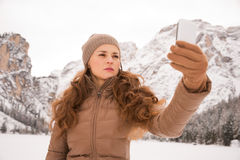 Woman taking photo outdoors among snow-capped mountains Royalty Free Stock Photos