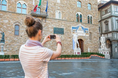 Woman taking photo of palazzo vecchio in florence Stock Photo