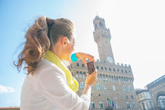 Woman taking photo of palazzo vecchio in florence Stock Images