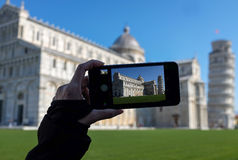 Woman taking photo with phone in Pisa, Italy Stock Images