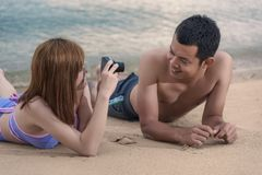 Woman taking photo picture of man smiling happy with camera. Woman taking photo picture of men smiling happy with camera of Thailand beach Stock Image