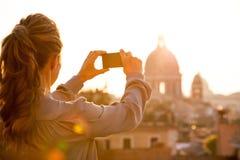 Woman taking photo of rome panorama on sunset Stock Image