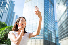 Woman taking photo by smart phone in Hong Kong Royalty Free Stock Image