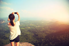 Woman taking photo with smart phone at mountain peak cliff Stock Image