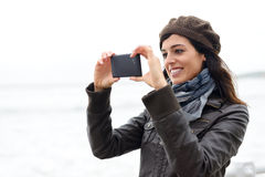 Woman taking photo with smartphone Stock Images