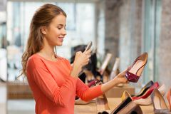 Woman taking photo by smartphone at shoe store Stock Photos