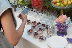 Woman taking photo of table with food, close-up, outdoors. Woman taking photo of table with food, close-up.  Catering service royalty free stock image