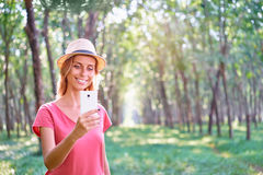 Woman taking photo. Technology and travel. Young woman taking photo of tree plantation on her smartphone Royalty Free Stock Images