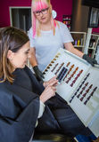 Woman taking a photo to the hair dye palette. Beautiful young women with hairdresser taking a photo with her smartphone to the hair dye palette Stock Photo