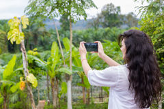 Woman Taking Photo Of Tropical Forest Landscape On Cell Smart Phone Back Rear View Stock Photos