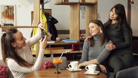 Three girlfriends are taking a photo on mobile phone in cafe. Friendly meeting in the cafe. Woman is taking a photo of two girlfriends on mobile phone in cafe stock video