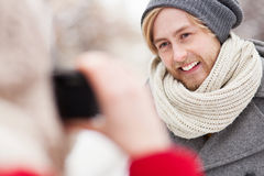 Woman taking photo of young man Stock Photography