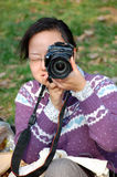Woman taking photograph. Portrait of Chinese woman taking photograph with digital camera outdoors Stock Photography