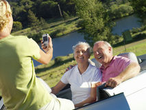 Woman taking photograph of senior couple by river royalty free stock photography