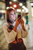Woman taking photograph with smartphone at night in the street royalty free stock photos