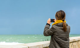 Woman taking photograph with smartphone on sea waterfront royalty free stock photography
