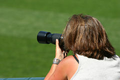 Woman taking photographs. Rear view of female sports photographer lying on grass taking pictures with long lens Stock Photos