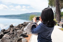 Woman Taking Photos Of Lake With Smartphone Royalty Free Stock Images