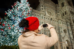 Woman taking photos near Christmas tree in Florence, Italy. Woman in white coat near Christmas tree taking photo of Duomo in the evening. She having holiday tour royalty free stock photos