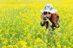 Woman taking photos at a rapeseed flowers. Stock Photos