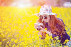 Woman taking photos at a rapeseed flowers. Stock Photography