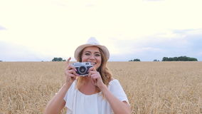 Woman taking photos with retro film camera on the field stock footage