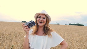 Woman taking photos with retro film camera on the field stock video