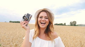 Woman taking photos with retro film camera on the field stock video footage