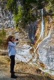 Woman taking photos of a waterfall Stock Photos