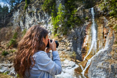 Woman taking photos of a waterfall Stock Images