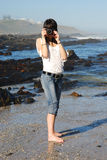 Woman taking picture on beach Stock Photography