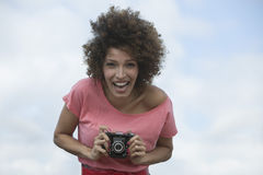 Woman taking a picture with a camera Stock Images