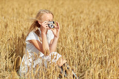Woman taking picture with camera in cereal field Stock Images