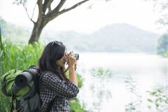 Woman taking picture with camera while hiking. Asian woman taking picture with camera while hiking near beautiful lake Royalty Free Stock Images