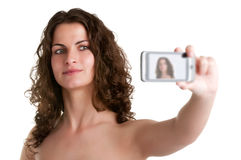 Woman Taking a Picture With a Cell Phone. Young woman taking a picture of herself with a cell phone, isolated in a white background Stock Photography