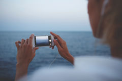 Woman taking picture on cell telephone camera while enjoying her weekend vacation overseas Royalty Free Stock Photography