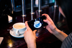 Woman taking a picture of coffee with smartphone Royalty Free Stock Photo