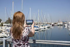 Woman taking picture with a digital tablet camera Stock Photos