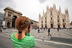 Woman taking picture of Duomo di Milano, Italy. Young woman taking picture of Duomo di Milano (Milan Cathedral), Milan, Italy, motion blurred people on square Stock Photos