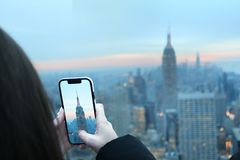 Woman taking a photo with cell phone of sunrise sunset manhattan