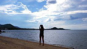 Woman taking picture of exotic beach with mobile stock footage